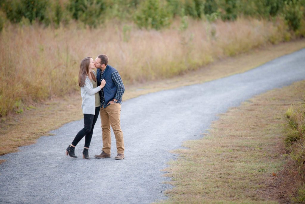 Couple kissing during engagement session at Garrard Landing Park GA