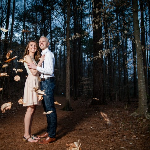 Atlanta engagement photography with leaves flying by in forest