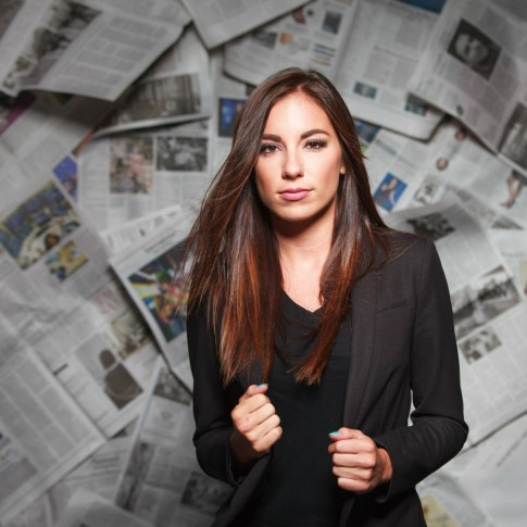 Beautiful woman posing in front of newspaper backdrop