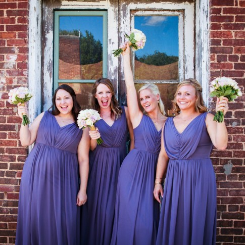 Bridesmaid getting excited in front of red brick wall