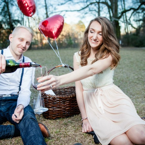 Engagement session with couple drinking red wine in a picnic scene