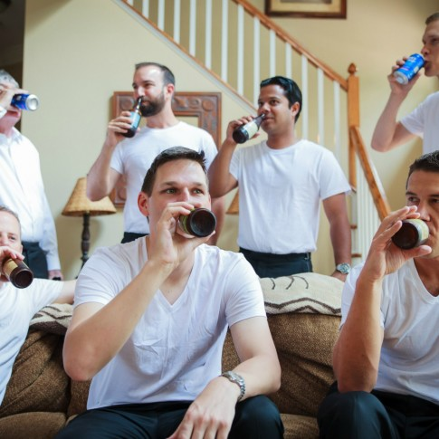 Groom groomsmen and dad drinking beer at cabin