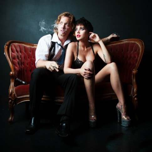 Man and women smoking and posing sitting on antique chair