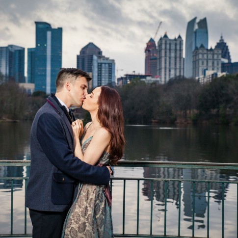 Piedmont Park Atlanta engagement session couple kissing with midtown as background