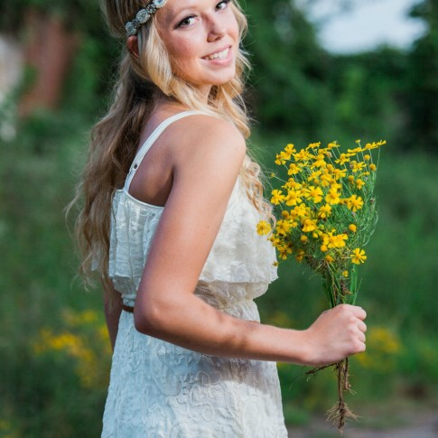Pretty girl holding yellow flower with white dress