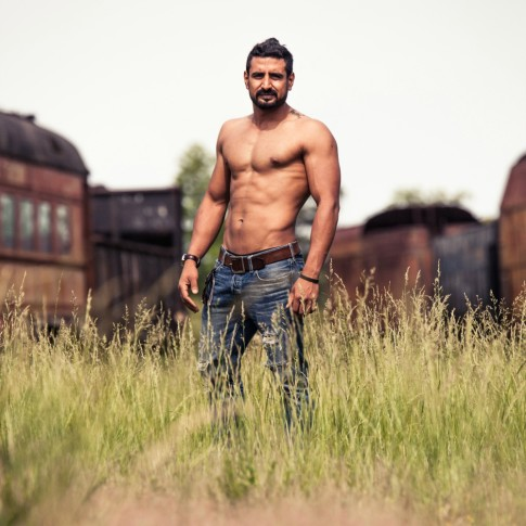 Well built man posing in front of train junkyard