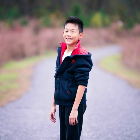 Young boy posing in front of long pathway with tall grass