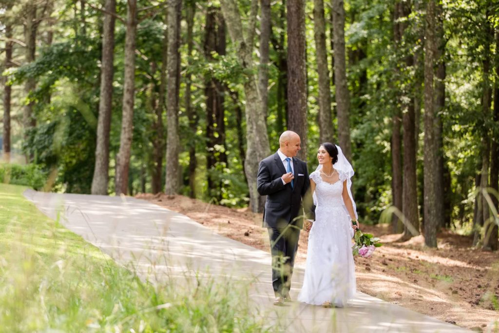 Bride and groom walking down the golf trail at The Standard Club Johns Creek